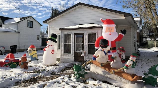 De multiples décorations de Noël gonflables sont installées devant la maison.