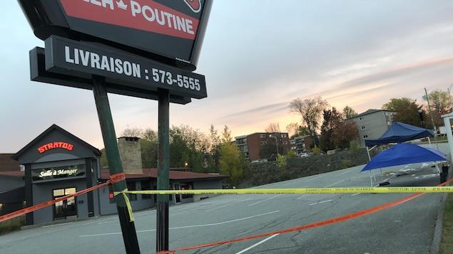 Un stationnement de restaurant avec une scène de crime.