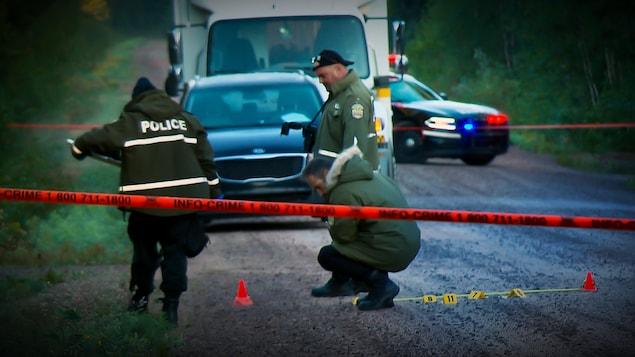 Des policiers colligent des indices sur la scène du crime.