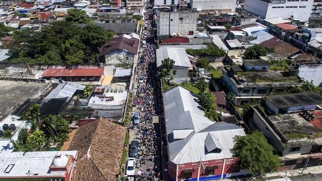 Une vue aérienne d'une colonne de migrants traversant une ville.