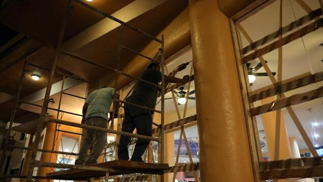 Deux employés juchés sur un escabeau effectuent des travaux.