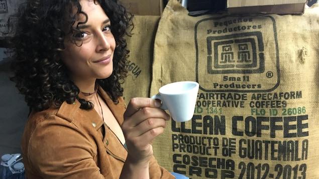 Une jeune femme, café à la main, pose devant un sac de grains de café.