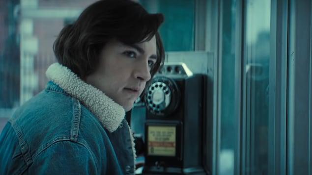 Un jeune homme vêtu d'une veste de jeans se tient dans une cabine téléphonique.