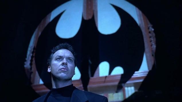 L'acteur regarde au loin avec l'ombre de Batman derrière lui.