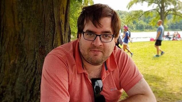 Michael McNeely tient un livre, assis devant un arbre.