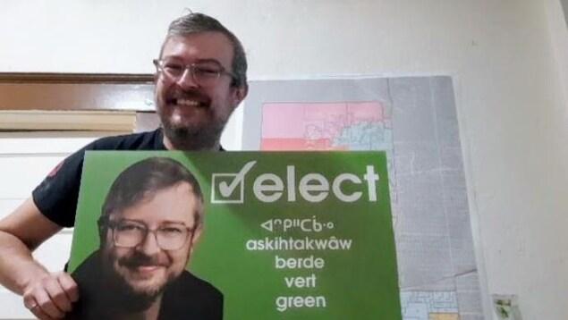 Le candidat Michel Wright présente sa bannière de campagne en plusieurs langues.