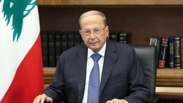Michel Aoun est assis derrière une table, devant une bibliothèque, à côté d'un drapeau du Liban.