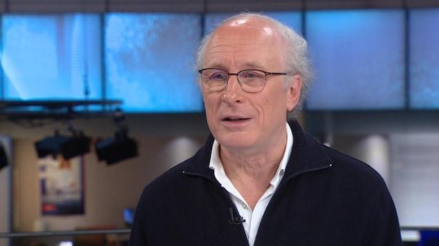 Un homme portant des lunettes est sur un plateau de télévision. Il sourit légèrement.