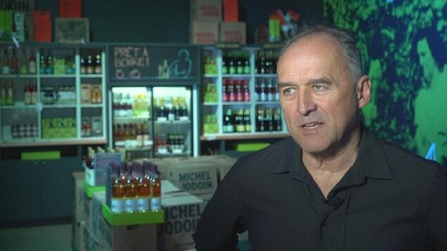 On voit M. Jodoin qui parle à la caméra; en arrière-plan on voit la boutique où l'on vend le cidre de glace.