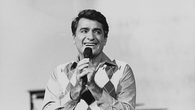 Un homme tient un micro et sourit.