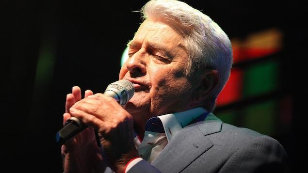 Michel Louvain chante au micro.