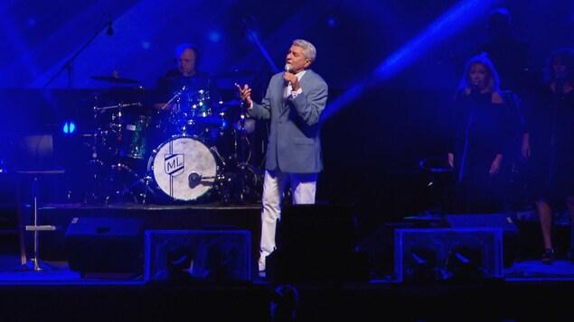 Michel Louvain sur scène avec ses musiciences.