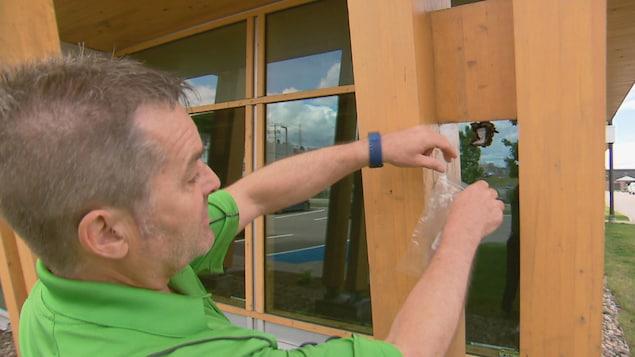 Michel Maheu utilise un sac de plastique pour sceller un nid de guêpes.