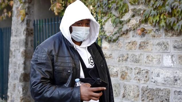 Un homme noir, masqué, marche dans une rue. Une écharpe lui soutient le bras gauche.