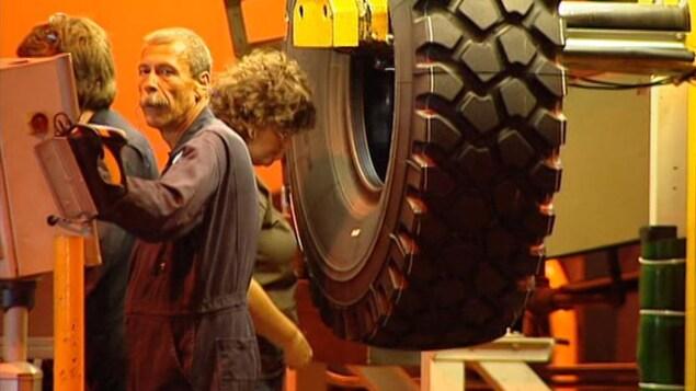 Trois travailleurs inspectent un pneu dans une usine.
