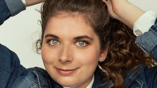 Une femme sourit et met ses deux mains au-dessus de sa tête. Elle a les yeux bleu clair et porte une veste en jean.