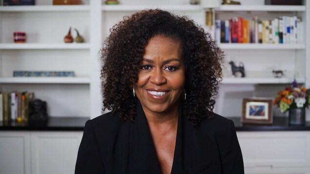Michelle Obama est vêtue de noir et sourit.