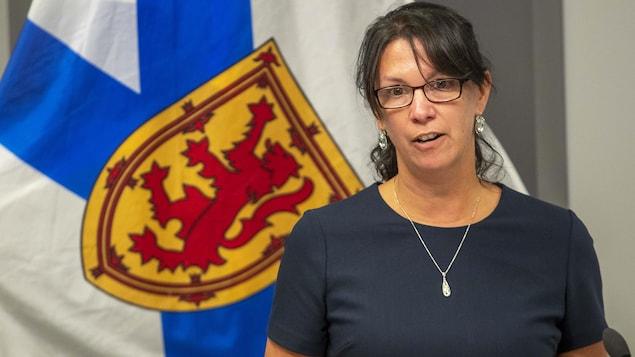 Michelle Thompson assise en conférence de presse devant un drapeau de la Nouvelle-Écosse.