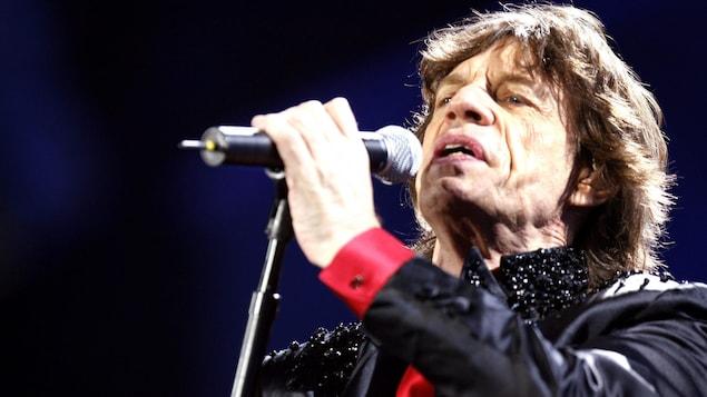 Mick Jagger, sur scène, tient un micro et chante.