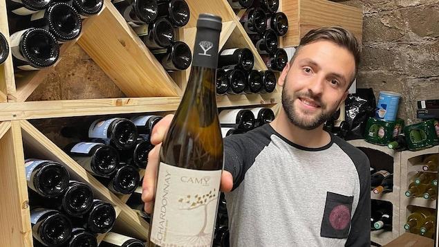 Mickaël Larrive tient une bouteille.