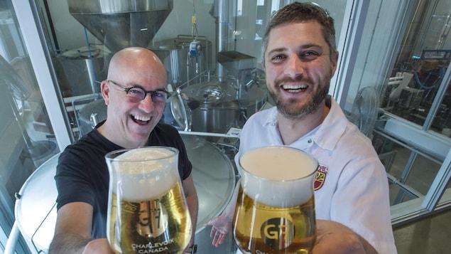 Le fondateur de la Microbrasserie Charlevoix, Frédérick Tremblay, et le brasseur Nicolas Marrant lèvent des verres de bière contenant La G7, devant des cuves de brassage dans la microbrasserie.
