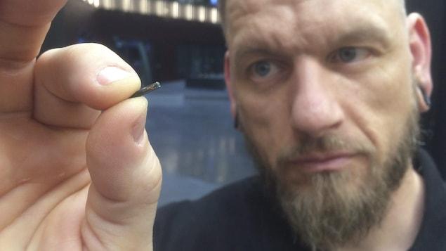 Jowan Osterlund de Biohax Suède tient une micropuce entre son pouce et son index.