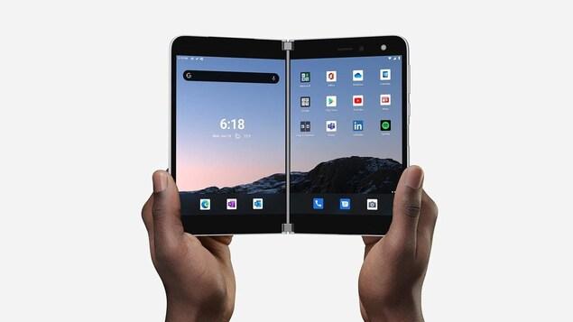Une personne tient le téléphone pliable Surface Duo, ouvert.