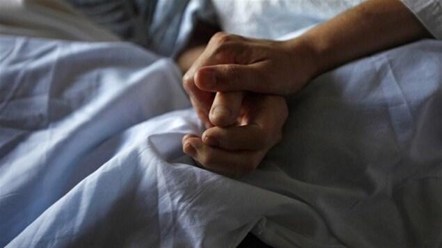 Les mains d'une patiente et d'une infirmière.