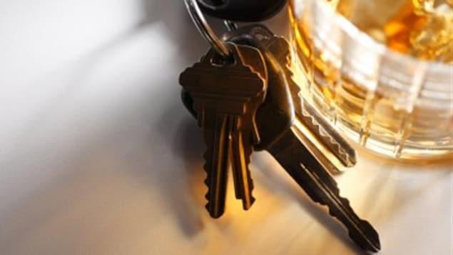 Un verre d'alcool sur une table avec un trousseau de clés
