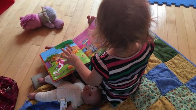 Une enfant qui feuillette un livre.