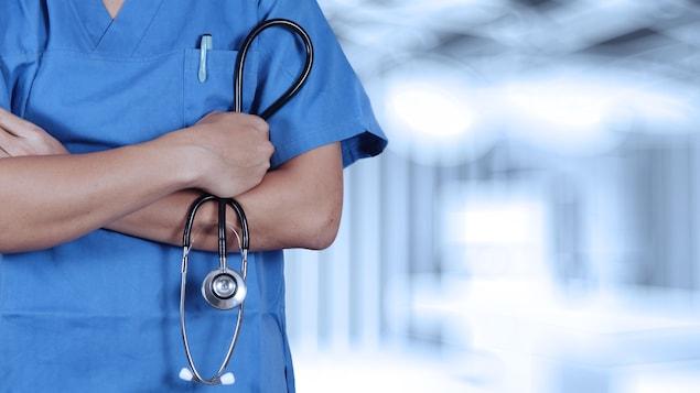 Photo générique d'un travailleur de la santé, les bras croisés, tenant un stéthoscope.