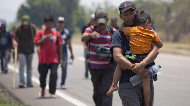 Un homme porte un enfant dans ses bras. Des hommes marchent derrière.