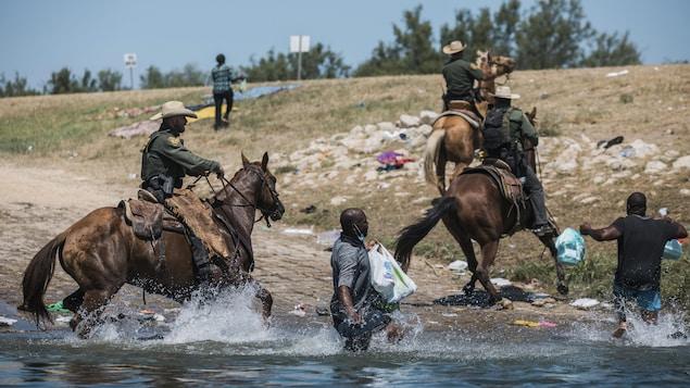 Des cavaliers américains sont dans le Rio Grande avec leurs chevaux et poursuivent des Haïtiens qui essaient de sortir de l'eau.