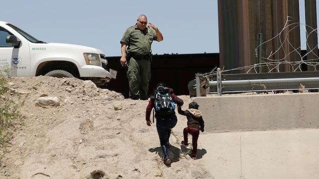 Une femme tient un enfant par la main et monte une pente en sable sur le sommet de laquelle se trouve l'agent frontalier.