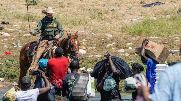 Une agent frontalier américain qui tente d'empêcher des migrants d'entrer dans un campement sur les rives du Rio Grande au Texas.
