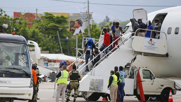 Des Haïtiens descendent d'un avion à Port-au-Prince, après avoir été expulsés des États-Unis.