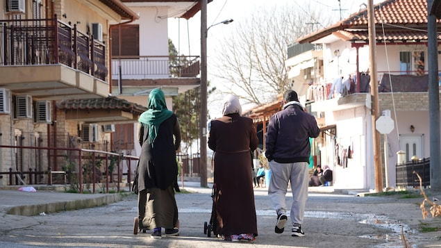 Un homme et deux femmes voilées marchent dans la rue.