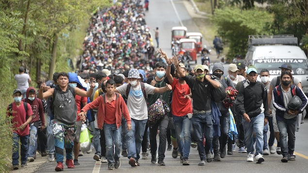 Une immense foule marche sur une route.