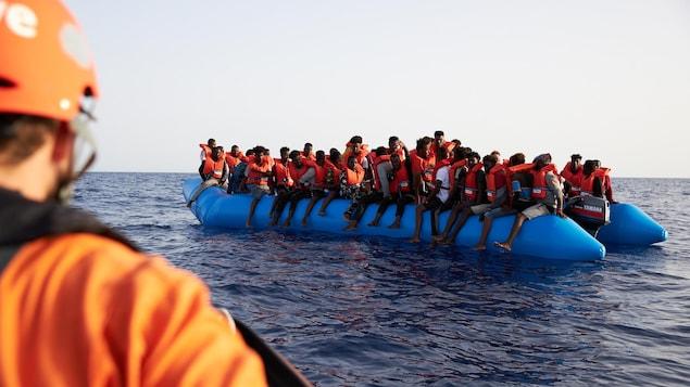 Des dizaines de migrants portant des gilets de sauvetage entassés dans un zodiac attendent d'être secourus au large de la Libye.