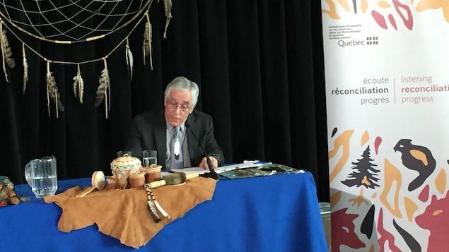 Le commissaire Jacques Viens parle lors d'une conférence de presse, assis à une table où sont déposés des objets traditionnels de communautés autochtones.