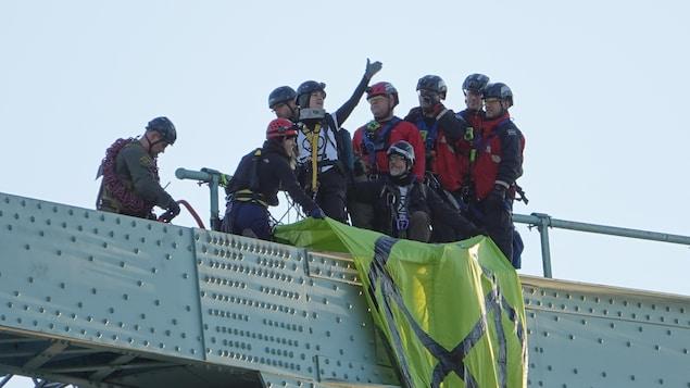 Une femme tient le bras en l'air en signe de victoire sur la structure du pont Jacques-Cartier.
