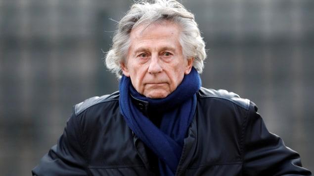 Photo de Roman Polanski vêtu d'un manteau de cuir, prise à l'extérieur.