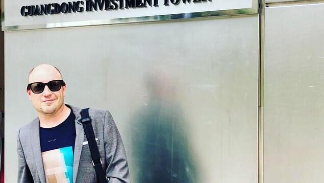 Mikael Charette devant une tour à bureaux en Chine.