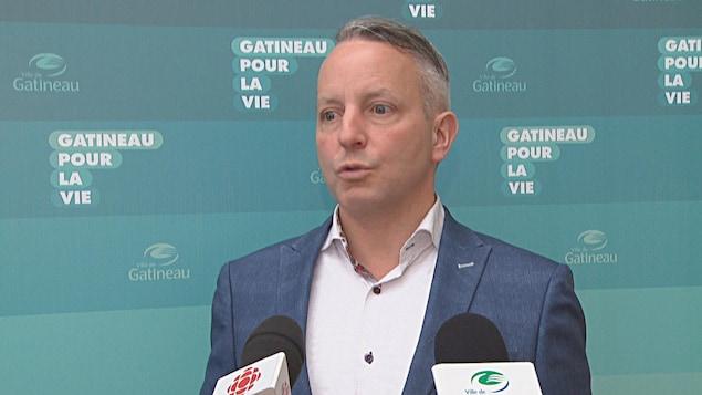 Mike Duggan s'adresse aux médias devant une bannière comportant le logo de la Ville de Gatineau.
