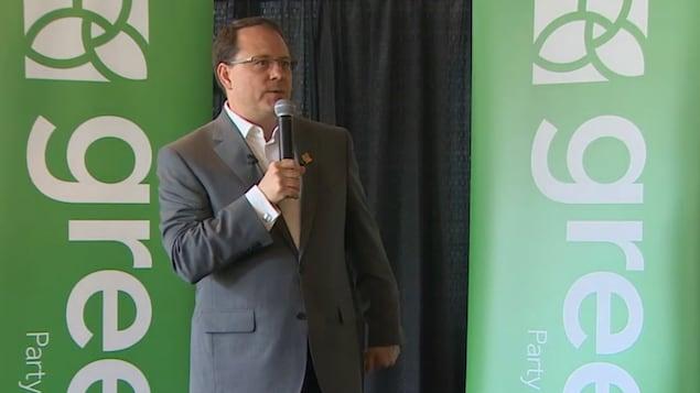 Mike Schreiner se tient sur une scène devant deux banderoles du Parti vert