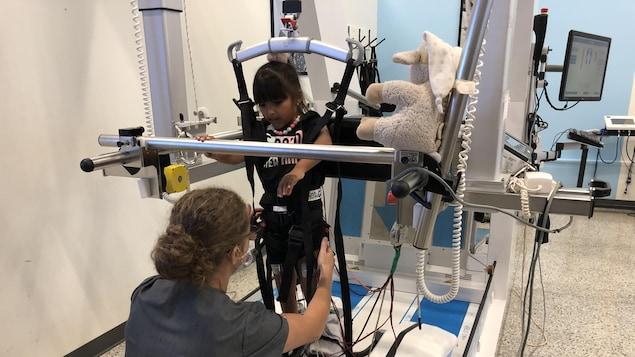 Une intervenante aide une fillette dans un appareil de réadaptation.