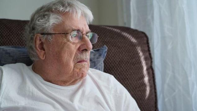Jon Overtveld, assis dans un fauteuil, regarde par la fenêtre.