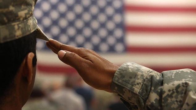 Un homme vêtu d'habits de l'armée fait le salut militaire devant un drapeau des États-Unis.