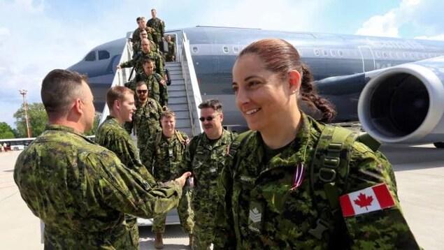 Une militaire canadienne arrive qui arrive en Lettonie en 2017.