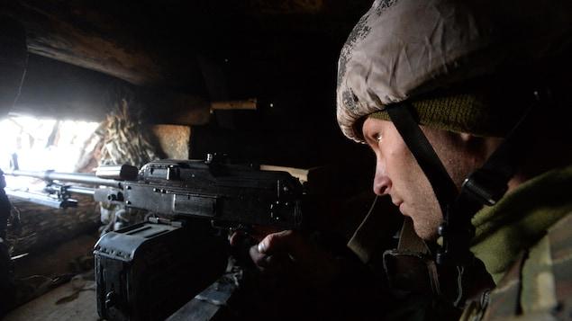 À l'affût, sa mitrailleuse prête à servir.